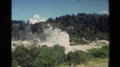 1981: a geyser puffing out billows of smoke in the forested wilderness NEW Stock Footage