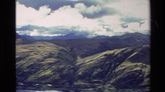 1982: a high view of a mountain range clearing a cloudy and blue sky and a Stock Footage