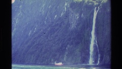 1982: a woman on a viewing deck looking at a mountain range and a waterfall NEW Stock Footage