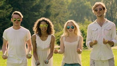 Cheerful young people throwing up colorful powder and hugging at summer party Stock Footage