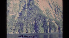 1982: boats moving through the waters of the lake in the valley of huge mountain Stock Footage