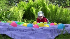 Funny baby girl crawl between colorful balls on plaid near fern plant. 4K Stock Footage