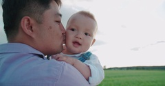 Portrait of happy Asian father holds his son for 1 year, slow motion, Sunny day Stock Footage