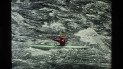 1980: a man in red dress and a cap is moving in a boat in sea GRAND TETON Stock Footage