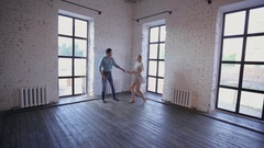 Young couple in love is learning to dance in the studio Stock Footage