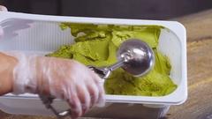 Green pistachios ice cream balls scooped by spoon Stock Footage
