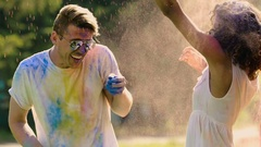 Excited friends throwing colorful powder, laughing and enjoying party together Stock Footage