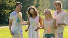 Young men throwing colorful powder on beautiful female friends by surprise Stock Footage