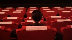 Asian ethnic girl sitting alone in empty red seat cinema theater Stock Footage