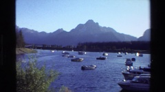 1980: dozens of boats anchored in a reservoir with jagged peaks in the distance Stock Footage
