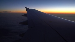 Hydrofoil of an airplane flying over clouds in the morning with a sunrise, 4K / Stock Footage