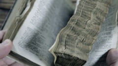 Flipping through pages of an old bible Stock Footage