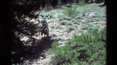 1981: a men wearing a cowboy hat riding a horse through the wilderness BRITISH Stock Footage