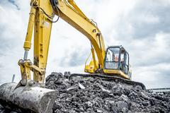 Excavator is preparing pile of ground for loading in truck on building site Stock Photos