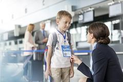 Flight attendant talking to child traveler in airport Stock Photos