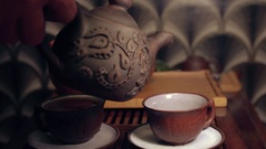The action of traditional Chinese tea ceremony. Pouring tea from tea pot in cup Stock Footage