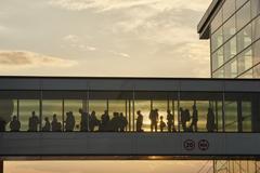 Silhouette people walking in airport sky bridge Stock Photos