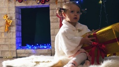 Girl opens Christmas gifts boxes near fireplace, decorated Cristmas tree Stock Footage