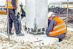 View on building site until workers are assembly concrete pillar Stock Photos
