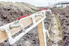 Few red taps are placed on plastic pipeline attached on wooden construction.. Stock Photos
