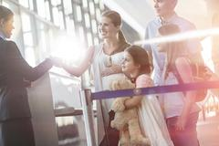 Flight attendant checking tickets of family in airport Stock Photos