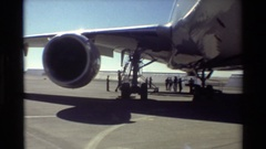 1981: group of men gathered underneath a large airplane, discussing something to Stock Footage