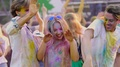 Excited young friends dancing together at paint festival, enjoying outdoor party HD Footage