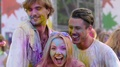 Drunk young friends covered in colorful paint performing crazy dance at festival HD Footage