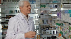Male druggist wears glasses at the pharmacy Stock Footage