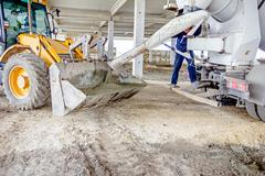 Workers are unloading concrete with shovel from excavator's front bucket. Stock Photos