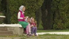 Three little girls from the Amish community sit on the curb and eating ice cream Stock Footage
