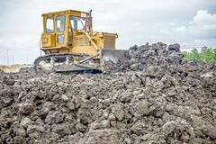 Heavy earthmover construction machine is moving earth at building site Stock Photos