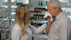 Female pharmacist offers remedy for cough to the customer Stock Footage