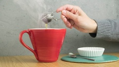 Tea cup and strainer in frozen moment with hot steam rising from the mug. Stock Footage