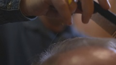MALE BARBER CUTTING HAIR OF MALE CLIENT WITH SCISSORS AND COMB Stock Footage