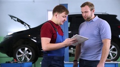 Customer and mechanic discuss upcoming car repair Stock Footage