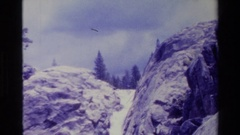 1980: water flowing in full force in between huge rocks and beautiful white Stock Footage