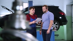 Car service. client and engineer discuss plan car repair Stock Footage