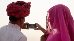 Indian couple looking back at the camera and taking photos of sunset at holy Pus Stock Footage