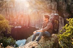 Adventure man sitting on rock Stock Photos
