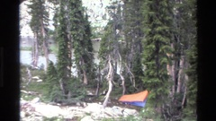 1980: backpackers camping in the wilderness surrounded by granite outcrops and Stock Footage