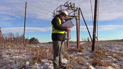 Electrician engineer writing near substation Stock Footage