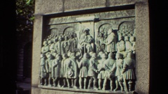 1982: stone carving on wall showing a king sitting on his throne surrounded by Stock Footage