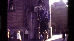 1982: pedestrians pass building where women and children stand at ornate arched Stock Footage