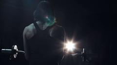 Strong toned young woman in a darkened gym Stock Footage