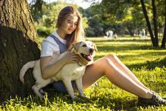 Young attractive blond woman playing with her dog in green park at summer Stock Photos