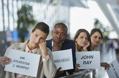 Bored chauffeurs waiting in a row with welcome signs at airport Stock Photos