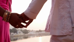 Close up of Indian couple holding hands, woman wearing many traditional wedding  Stock Footage
