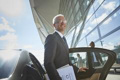 Smiling businessman arriving at airport getting out of town car Stock Photos