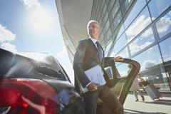 Businessman arriving at airport getting out of town car Stock Photos